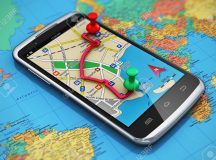Mobile GPS navigation, travel and tourism concept: macro view of modern black glossy touchscreen smartphone with GPS navigation application, magnetic compass, pen and group of pushpins on world map with selective focus effect